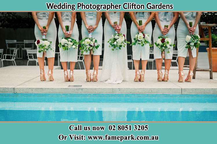 Behind photo of the Bride and the bridesmaids holding flowers near the pool Clifton Gardens NSW 2088