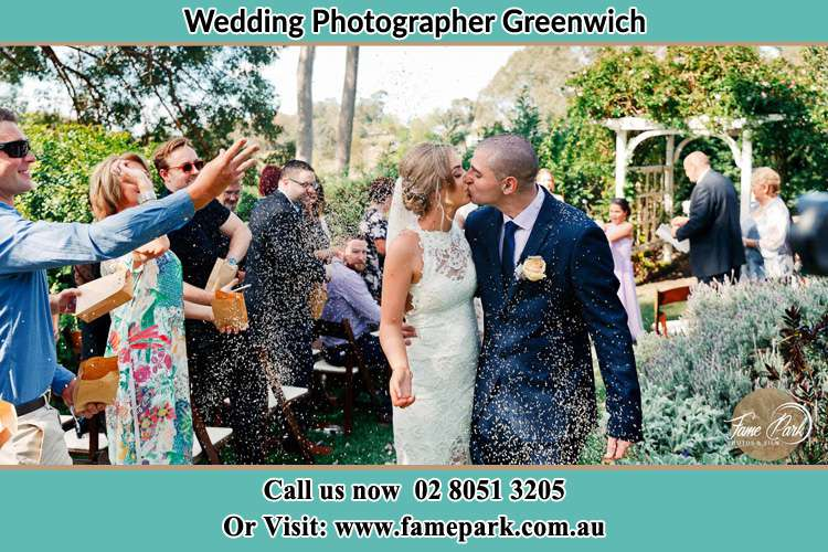 Photo of the Bride and the Groom kissing while showering rice by the visitors Greenwich NSW 2065