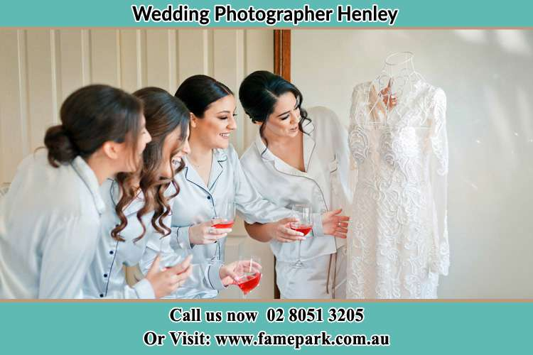 Photo of the Bride and the bridesmaids looking at the wedding gown Henley NSW 2111