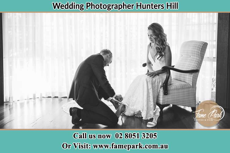 The Bride is being helped by the Groom trying to put on her shoes Hunters Hill NSW 2110