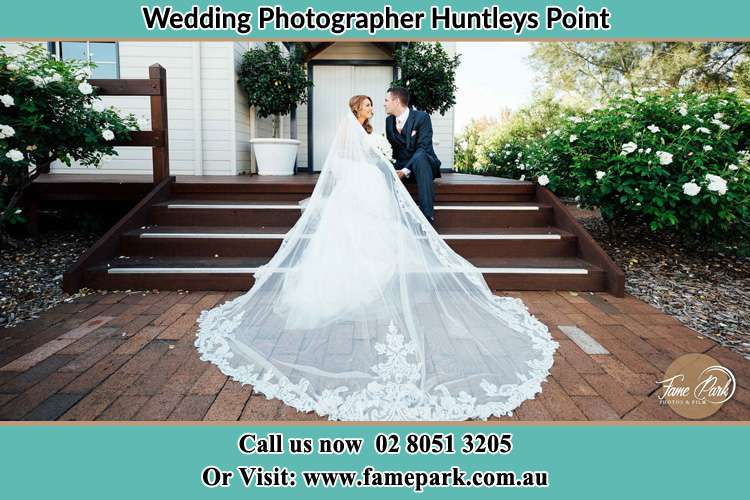 Photo of the Bride and the Groom looking each other while sitting at the staircase Huntleys Point NSW 2111