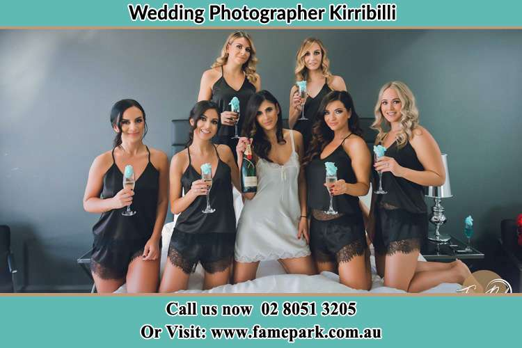 Photo of the Bride and the bridesmaids wearing lingerie and holding glass of wine on bed Kirribilli NSW 2061