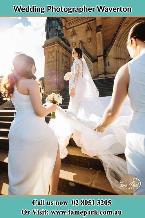 Photo of the Bride smiling on the bridesmaid holding the tail of her wedding gown at the front of the church Waverton NSW 2060