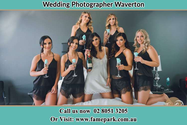 Photo of the Bride and the bridesmaids wearing lingerie and holding glass of wine on bed Waverton NSW 2060