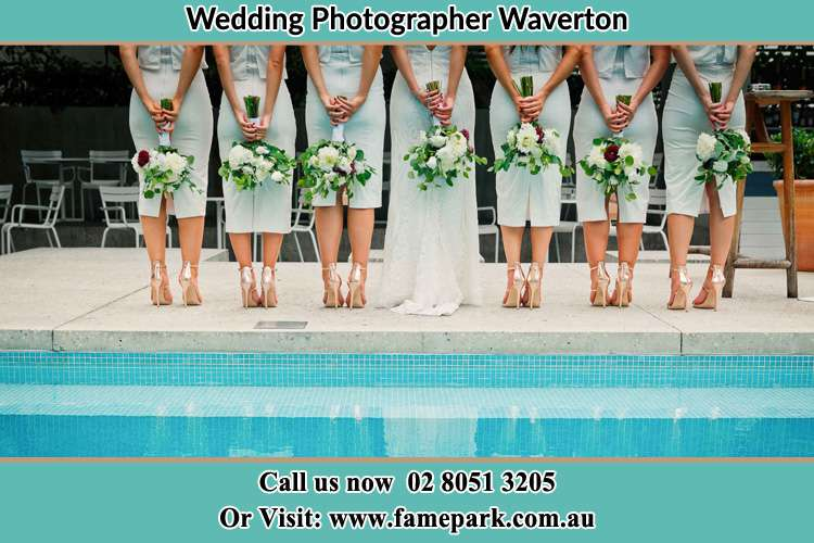 Behind photo of the Bride and the bridesmaids holding flowers near the pool Waverton NSW 2060